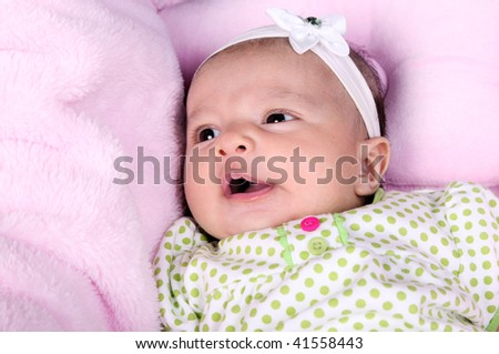 Beautiful smiling baby on a blanket pink