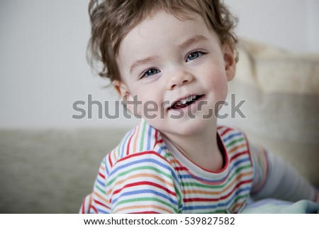 Beautiful smiling baby with big eyes in a bright room. Lifestyle. #539827582