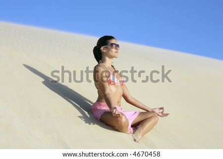 beautiful smiling bikini dressed young brazilian  woman medtating on lotus posture on the sand dune of  jericoacoara ceara state near fortaleza