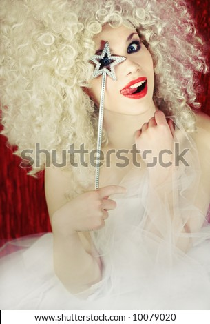 Beautiful smiling blond fairy girl with magic wand, pulling a funny face