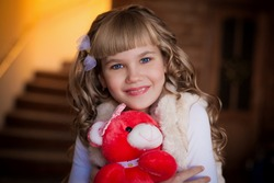 beautiful  smiling  blonde  curly  girl   with red soft  toy