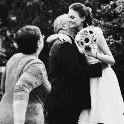 beautiful smiling bride with a bouquet hugging his father black and white