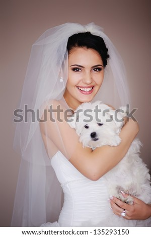 Beautiful Smiling Brunette Bride with small dog posing