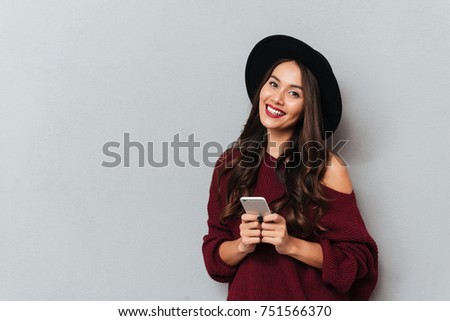 Beautiful smiling brunette woman in black hat holding mobile phone and looking at camera, isolated on gray background #751566370