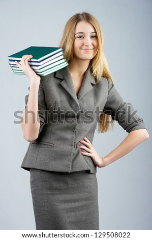 Beautiful smiling business woman with with pile of books in her hand.