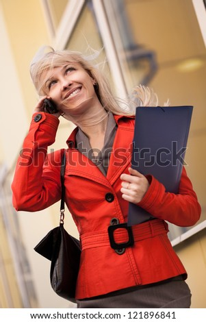 Beautiful smiling businesswoman calling by phone outdoors