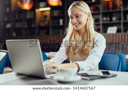 Beautiful smiling Caucasian blonde female blogger dressed smart casual sitting in cafeteria and using laptop. #1414607567