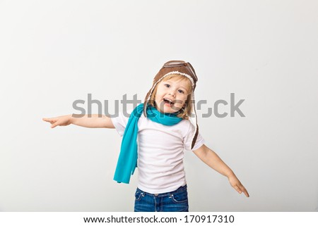 Beautiful smiling child (girl) in helmet on a white background playing with a plane. Vintage pilot (aviator) concept