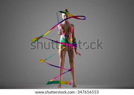 Beautiful smiling cool young fit gymnast woman in colorful sportswear working out, performing rhythmic gymnastics element with multi-colored art ribbon, doing horizontal snakes, dancing, studio