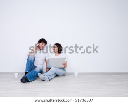 Beautiful smiling couple relax in the empty room with laptop  - new home