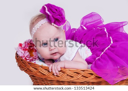Beautiful smiling cute baby happy adorable child. funny child  in a beautiful magnificent skirt lies in a basket