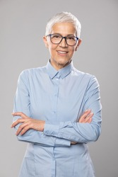 Beautiful smiling cute senior businesswoman with glasses and a blue shirt with short white hair and glasses posing in front of gray background