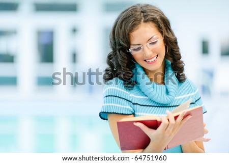 Beautiful smiling dark-haired woman in blue sweater and glasses reads interesting red book against spacious hall.