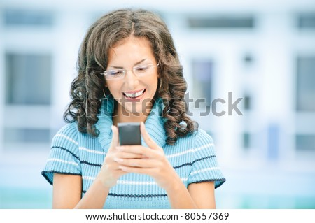 Beautiful smiling dark-haired woman in dark blue sweater and glasses on mobile phone against spacious light hall.