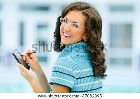 Beautiful smiling dark-haired woman in dark blue sweater and glasses writes with help stylus on pocket computer against spacious light hall.