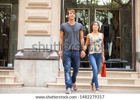 Beautiful smiling ethnically diverse young couple enjoying city break holiday, holding hands walking together in shopping mall with clothing stores, outdoors. Consumers leisure recreation lifestyle.