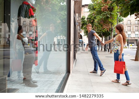 Beautiful smiling ethnically diverse young couple enjoying city break holiday trip, holding hands walking together in shopping mall clothing stores, outdoors. Consumers leisure recreation lifestyle.