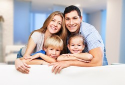Beautiful smiling family in room on couch