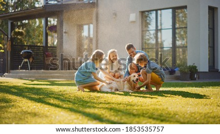 Beautiful Smiling Family of Four Cuddling Happy Golden Retriever Dog on the Backyard Lawn. Idyllic Family Cuddling Loyal Pedigree Dog Outdoors in Summer House Backyard.