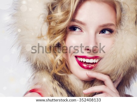 Stock Photo Beautiful smiling fashion model face with red lips and fur hood
