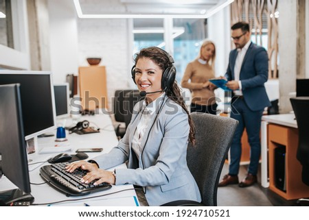 Beautiful smiling female call center worker accompanied by her team working in the office.