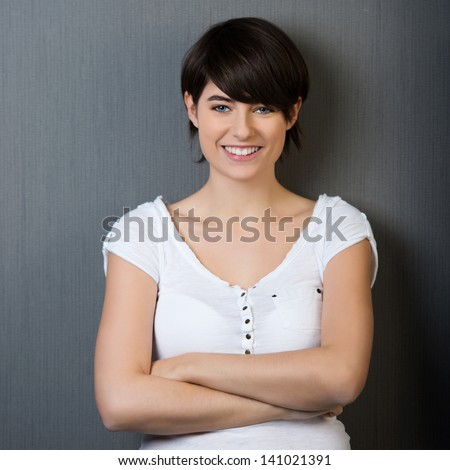 Beautiful smiling female leaning on a grey wall with arms crossed
