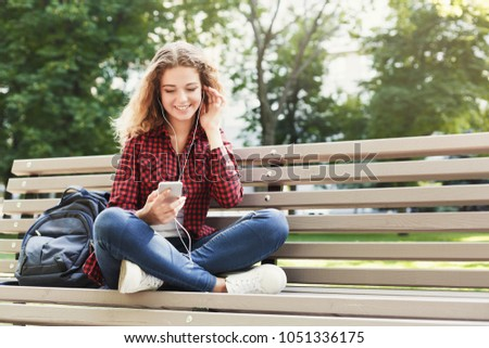 Beautiful smiling female sitting and listening music on the smartphone on the bench outdoors. Technology, social media, education and freelance concept, copy space #1051336175