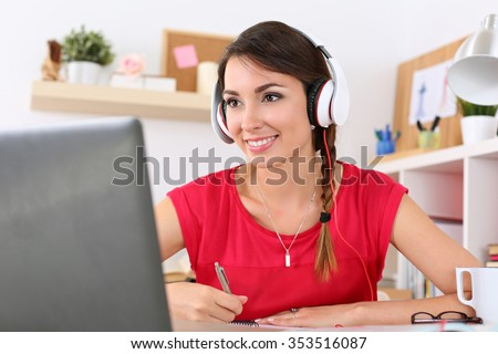 Beautiful smiling female student using online education service. Young woman looking in laptop display watching training course and listening it with headphones. Modern study technology concept