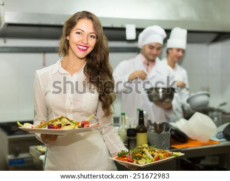 Beautiful smiling female waiter taking dish from kitchen in cafe