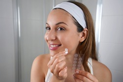 Beautiful smiling girl applying acne treatment anti-pickel patch on a pimple in bathroom