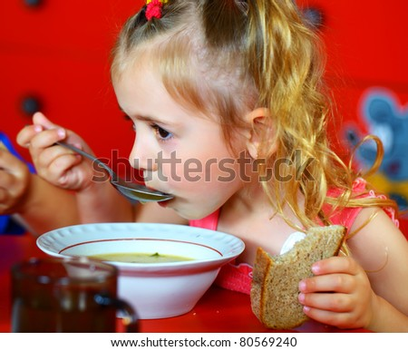 Beautiful smiling girl eating soup from a plate