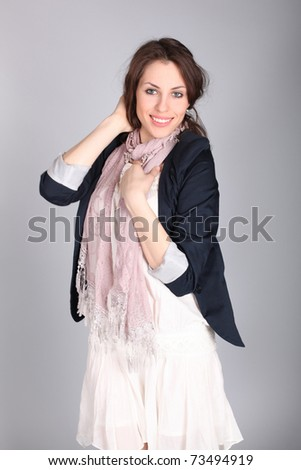 Beautiful smiling girl in a blue coat over gray background. Studio shot.