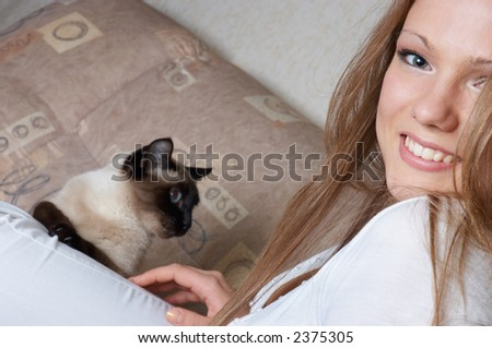 beautiful smiling girl in white with cat sitting on her leg