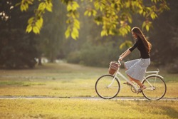 Beautiful smiling girl is riding the bicycle in the park