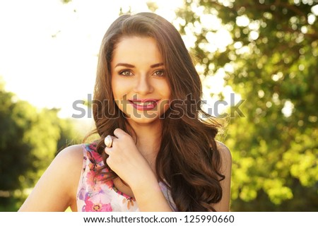 beautiful smiling girl looking at you against spring green bokeh background
