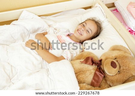 Beautiful smiling girl lying on bed with big teddy bear