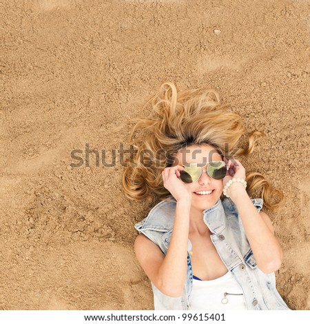 beautiful smiling girl lying on the sand