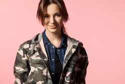 Beautiful smiling girl on a pink background in a military jacket with camouflage pattern