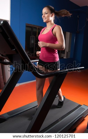 Beautiful smiling girl running on treadmill in the gym.