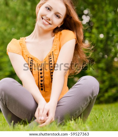 Beautiful smiling girl sits on green lawn in lotus pose.