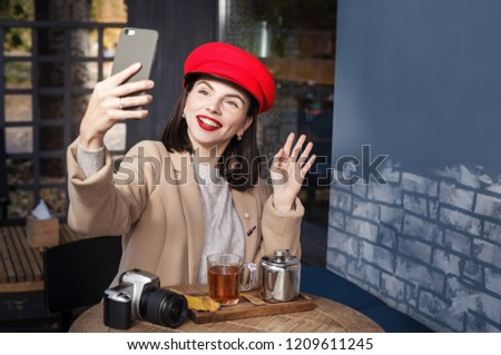 Beautiful smiling girl sitting in a cafe and using a smartphone #1209611245