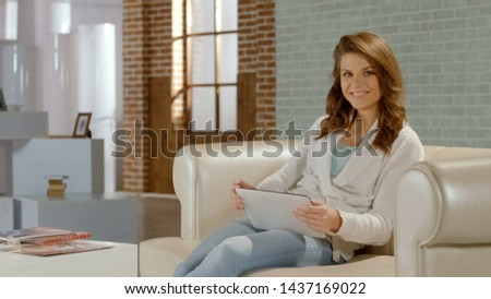 Beautiful smiling girl sitting on couch with tablet, ad of online shopping