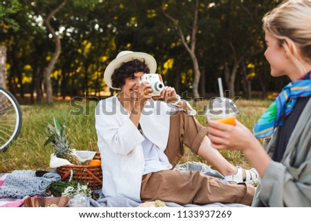 Beautiful smiling girl sitting on picnic blanket happily taking photos of friend on polaroid camera on picnic in park