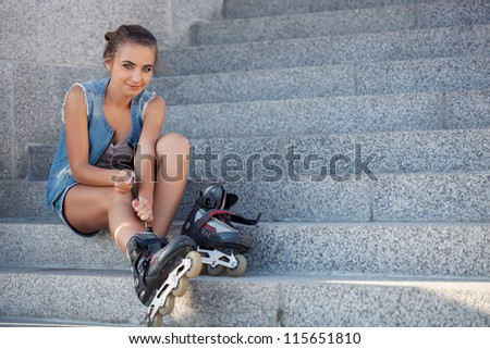 beautiful smiling girl sitting on the stairs and puts on skates and looking at camera