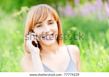 Beautiful smiling girl speaks by mobile phone against summer green nature.