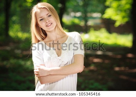 Beautiful smiling girl standing with folded hands over green summer background