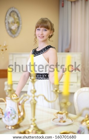 Beautiful smiling girl stands next to classic white table with set of dishes and candles.