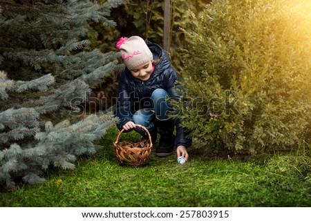 Beautiful smiling girl taking Easter egg form under the bush a backyard