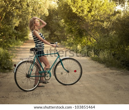 beautiful smiling girl with a bicycle on the road