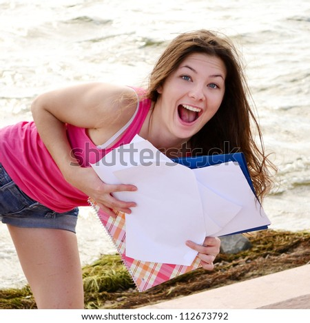 beautiful smiling girl with notebook at beach